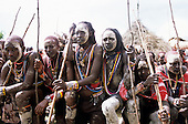 Lolgorian, Kenya. Siria Maasai; Eunoto ceremony; line of kneeling moran with white ochre body paint.