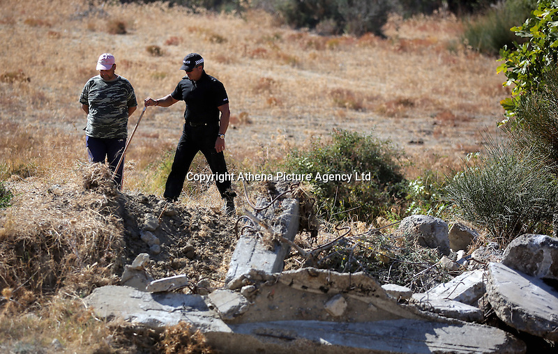 Pictured: A police officer and a workers involved with clearing the new site of the search, where rubble was deposited from the farmhouse where Ben Needham disappeared from in Kos, Greece. Thursday 06 October 2016<br />Re: Police teams led by South Yorkshire Police, searching for missing toddler Ben Needham on the Greek island of Kos have moved to a new area in the field they are searching.<br />Ben, from Sheffield, was 21 months old when he disappeared on 24 July 1991 during a family holiday.<br />Digging has begun at a new site after a fresh line of inquiry suggested he could have been crushed by a digger.