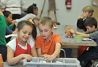 NWA Democrat-Gazette/MICHAEL WOODS • @NWAMICHAELW<br /> Gabriella Zelaya, 6, and Cooper Sudduth, 7, search for tiles as they work on creating mosaic flower pots Wednesday, March 23, 2016, during  the Spring Break Camp at the Community Creative Center in Fayetteville.  The spring break camp gave kids a chance to create colorful art  inspired by the joyfulness of Spring with activities including watercolor painting, drawing with soft pastels, mosaic sculptures, and mosaic flower pots for the garden.