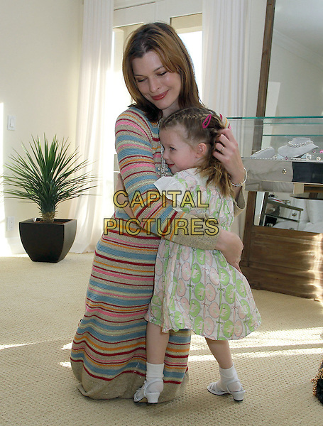 MILLA JOVOVICH & daughter  Ever Gabo.At The Hospitality Suite Hosted by Pacal Mouawad held At The Nivea For Men's Mansion,  Beverly Hills, CA, USA, .14th January 2011..full length blue pink beige striped dress sweater jumper mother child family kid necklace shoes kneeling on floor hugging hug nude cream .CAP/ADM/KB.©Kevan Brooks/AdMedia/Capital Pictures.