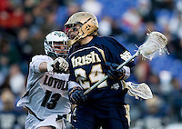 Michael Crimmins (13) of Loyola checks Eric Keppeler (24) of Notre Dame as he moves through the midfield during the Face-Off Classic in at M&T Stadium in Baltimore, MD