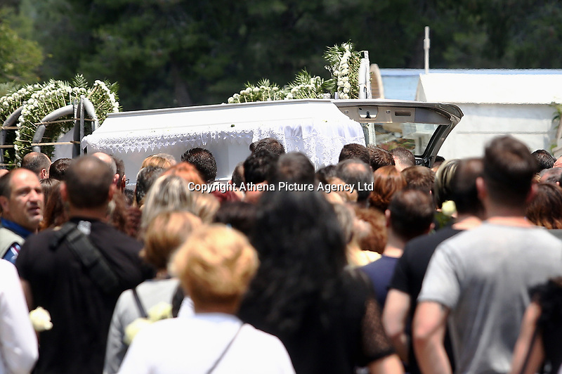 "Pictured: The coffin of Marios Souloukos at his funeral the Acharnes Cemetery, Athens, Greece. Saturday 10 June 2017<br /> Re: An 11 year old boy has been shot dead by a ""stray bullet"" during a school celebration in Acharnes (Menidi) area, in the outskirts of Athens, Greece.<br /> Marios Dimitrios Souloukos ""complained to his mum"" who works as a teacher at the 6th Primary School of Acharnes that he was feeling unwell, he then collapsed with blood pouring out from the top of his head.<br /> His mum tried to revive him assisted by other teachers while his schoolmates who were reportedly upset, were hurriedly removed by their parents.<br /> According to locals an ambulance arrived 25 minutes late.<br /> Hundreds of police officers have been deployed in the area and have raided many properties.<br /> Shells matching the fatal bullet which hit the boy on the top of his head were found in a house yard nearby.<br /> Local people reported hearing shots being fired at a nearby Romany Gypsy camp before the fatal incident.<br /> The area has been plagued with criminality during the last few years."