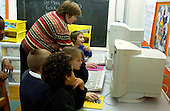 MR / Schenectady, NY.Yates Arts in Education Magnet School, Grade 2.Arts-Themed Urban Elementary School.Students use computers at free time. Teacher helps boy (7)..MR: Car19 Pom3.© Ellen B. Senisi