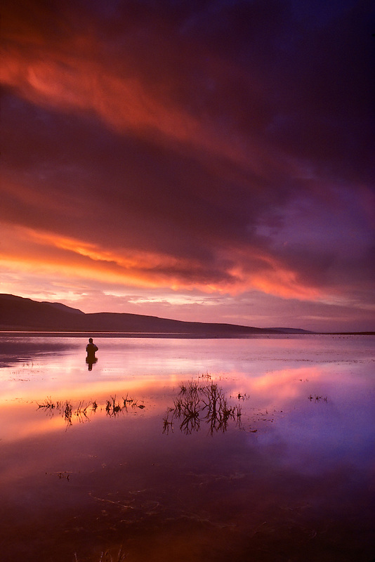 Fly fisherman on Mann Lake with sunrise. Oregon.