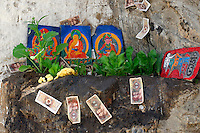Shrine at Palha Lupuk cave temple with carved painted stone of Sakyamuni, the Buddha, mani stone with mantra  Om Mani Padme Hum, money stuck to rock with yak butter, Lhasa, Tibet, China.