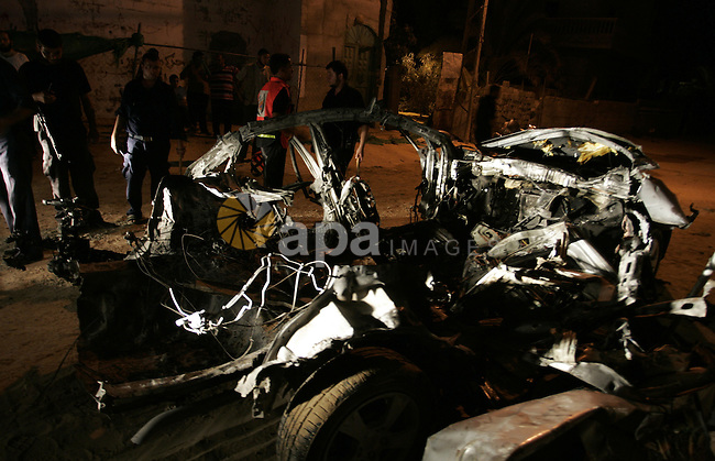 Palestinians look at the wreckage of a car after it was hit by an Israeli missile, killing an Islamic Jihad militant in Rafah, southern Gaza Strip, early Wednesday, Aug. 24, 2011. The Israeli military said the gunman had smuggled weapons into Gaza and was involved in militant activity in Egypt's Sinai peninsula, near Israel's southern border. Photo by Abed Rahim Khatib