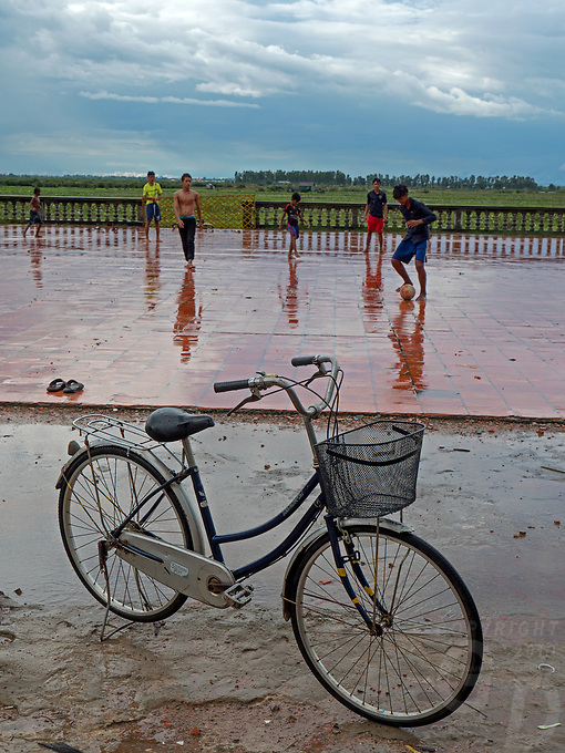 Overlooking the vast rice fields from a Monastery teenagers and children playing during a heavy Monsoon rain shower near the Tonle Sap lake, Cambodia
