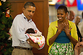 United States President Barack Obama holds one month old Adeline Valentina Hernandez Whitney as first lady Michelle Obama looks on Sunday, December 25, 2011 in Kaneohe, Hawaii.   The President and Mrs. Obama make their annual trip to greet current and retired members of the U.S. military and their families as they eat a Christmas Day meal at Anderson Hall mess hall at Marine Corps Base Hawaii.  .Credit: Kent Nishimura / Pool via CNP