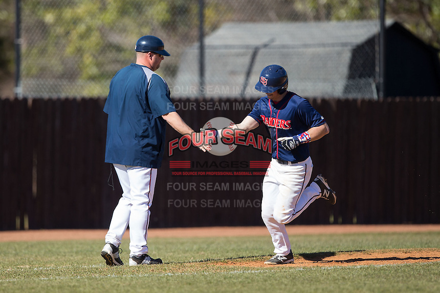 Shippensburg Raiders head coach Matt Jones slaps hands with Mike Marcinko (2) as he rounds third base after hitting a 3-run home run against the Belmont Abbey Crusaders at Abbey Yard on February 8, 2015 in Belmont, North Carolina.  The Raiders defeated the Crusaders 14-0.  (Brian Westerholt/Four Seam Images)