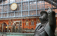 "John Betjeman (detail), larger-than-lifesize bronze statue, 2007, Martin Jennings, St Pancras International, with ""The Meeting Place"", by Paul Day, 2007, and the famous St. Pancras Clock in the background, London, UK. Picture by Manuel Cohen"