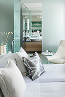 A guest bedroom with an en-suite bathroom beyond. A palette of greys and blue give the room a cool, restful ambiance.