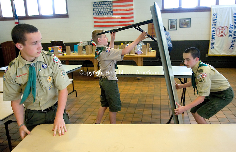 MIDDLEBURY CT. 03 May 2015-050315SV11-From left, Bob Holmes, 14, Ethan Harrington, 10, and Tom Holmes, 13, sets up tables for the Boy Scout Troop 444 Pasta dinner at the firehouse in Middlebury. The fundraiser serves about 300 dinners and the proceeds pay for their camping trips and expenses through out the year. <br /> Steven Valenti Republican-American