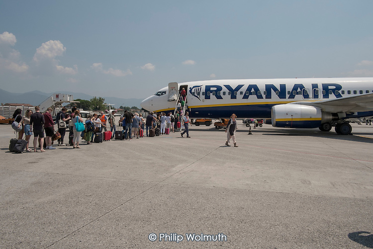 Passengers queue to board a Ryanair plane at Pisa airport, Italy.