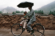 September, 1985. Shaanxi Province, China, in the area of Wuqi, a policeman father takes his son to school in the rain on bicycle.