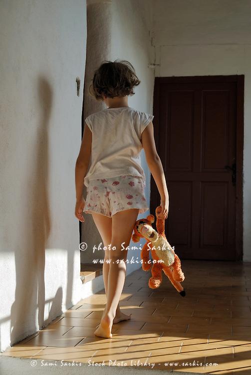 Seven year old girl walking along a hallway in her pyjamas.