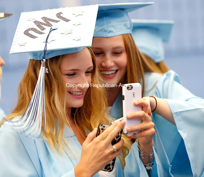 Oxford, CT- 15 June 2015-061515CM04-  Oxford High School graduates Casey Fitzgerald, left, and Mackenzie Folsom enjoy a laugh while looking at a cell phone before the start commencement exercises in Oxford on Monday.   Christopher Massa Republican-American