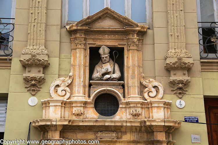 Statue of Christian bishop carved stonework of the cathedral church building in city of Valencia, Spain