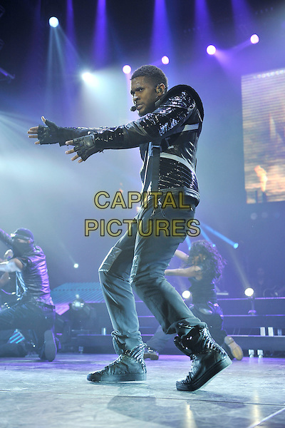 USHER (USHER RAYMOND).Performing live at the O2 Arena, London, England. .February 3rd, 2011.stage concert live gig performance music full length black leather jacket jeans denim singing hands arm dancing side.CAP/MAR.© Martin Harris/Capital Pictures.