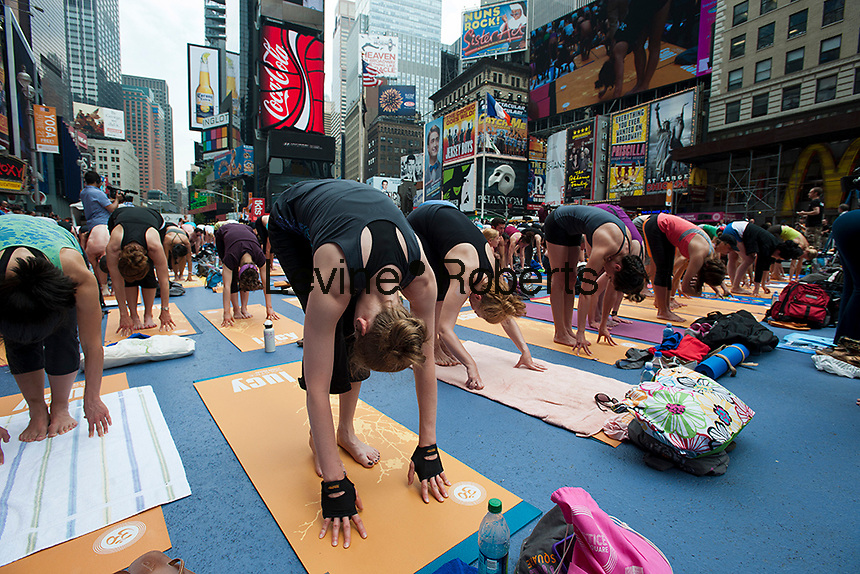 Thousands of yoga practitioners in Times Square in New York participate in a group Bikram Yoga class observing the Summer Solstice at 1:16 PM on Tuesday, June 21, 2011. The classes given throughout the day attract thousands of students of various levels who practiced their art and attempted to find tranquility and transcendence amidst the cacophony and chaos in Times Square on a busy Tuesday afternoon. (© Richard B. Levine)