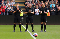 Match officials Jon Moss (C) with Edward Smart and Andrew Halliday applaud in tribute to Swansea president Gwilym Joseph who died during the English Premier League soccer match between Swansea City and Manchester United at Liberty Stadium, Swansea, Wales, UK. Saturday 18 August 2017