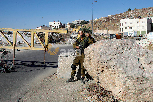 Israeli soldiers close a barrier blocking the road at a southern entrance of Hebron on July 2, 2016, after Israeli troops locked down the occupied West Bank city following Palestinian attacks. Israeli forces locked gates and set barriers blocking access routes to the villages in the area and closed all the exits to the southern Palestinian city except for the northern one near the village Halhul. The army had on July 1 announced the closure as well as its intention to deploy two additional battalions to the area, following two deadly attacks. Photo by Wisam Hashlamoun
