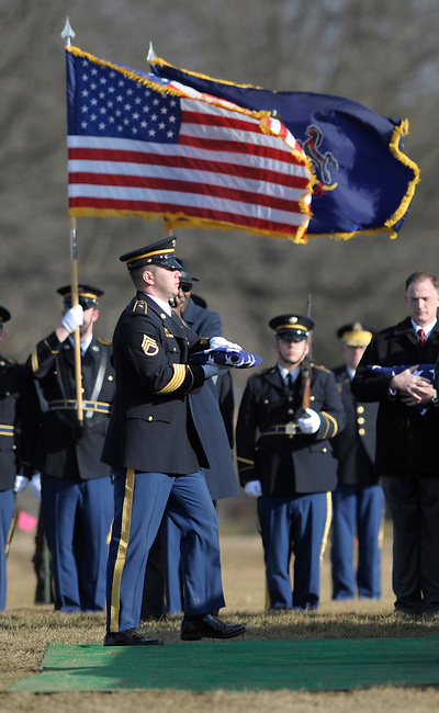 A member of the Military Honor Guard carries a flag to a family during the first burials of American servicemen at the new Washington Crossing National Cemetery Wednesday, Jan. 20, 2010 in Newtown, Pa. (AP Photo/Bradley C Bower)