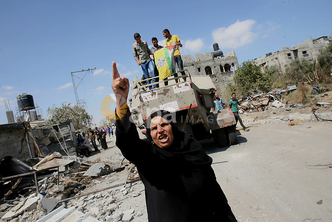 A Palestinian woman gestures in front of an Israeli military equipment, which witnesses said left behind by Israeli forces during a ground offensive, east of Khan Younis in the southern Gaza Strip July 26, 2014. The Gaza Health Ministry said 18 members of a single family were killed by Israeli tank shelling in the southern Gaza Strip shortly before the truce took effect at 8 a.m. (6 a.m. British Time). An Israeli military spokeswoman said she was checking the report. A 12-hour humanitarian truce went into effect on Saturday after Israel and Palestinian militant groups in the Gaza Strip agreed to a U.N. request for a pause in fighting and efforts proceeded to secure a long-term ceasefire moved ahead. Photo by Eyad Al Baba