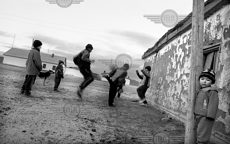 Young boys play football with one of the two soccer balls in their village.