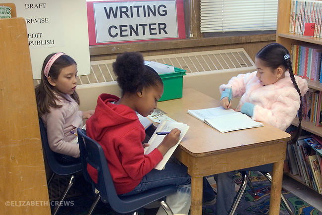Oakland CA 2nd grade students concentrating on writing projects in classroom Writing Center