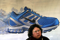 A woman sits in front of a Nike Advertisement at a bus stop in downtown Shanghai, China..