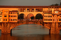 Detail of central section, Ponte Vecchio, Florence, Tuscany, Italy, pictured on June 8, 2007, in the evening. The Ponte Vecchio, or Old Bridge, crosses the River Arno at its narrowest point. The original bridge, possibly Roman and first documented in 999, was swept away in a flood in 1117, rebuilt, swept away again in 1333 and rebuilt in 1345. In 1565 Cosimo de Medici commissioned Vasari to design a corridor, above the famous shops along the bridge, connecting the Palazzo Vecchio to the Pitti Palace. In 1593 the Medicis prohibited butchers, the traditional occupants, from the shops which were soon taken by Goldsmiths. Florence, capital of Tuscany, is world famous for its Renaissance art and architecture. Its historical centre was declared a UNESCO World Heritage Site in 1982. Picture by Manuel Cohen.