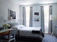 The stylish guest bedroom is in restful shades of pink and grey. Next to the double bed stands a writing table and chair upholstered in grey and pink fabric. Two wall lights provide the bedside lighting.