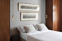 The collection of antique, seafaring illustrations continues upstairs with two pictures of harbours hung above this bed