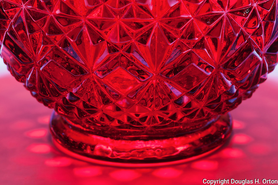 Looking into a red, cut glass, crystal, candy bowl, lying down with light from above, reflection and shadow on white gradiated background.