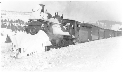 3/4 fireman's-side view of D&amp;RG #170 with a passenger train at Cumbres in the snow.  Notice that the headlight is damaged and that the engine does not have a pilot plow.  Some distress is apparent here.<br /> D&amp;RG  Cumbres, CO  Taken by Lively, Charles R. - 5/21/1915