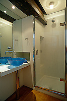 A small bathroom with a tiled shower and a blue glass wash basin