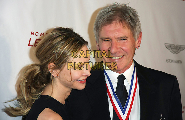 "CALISTA FLOCKHART, HARRISON FORD .8th Annual ""Living Legends of Aviation"" Awards held at The Beverly Hilton, Beverly Hills, California, USA, .21st January 2011..portrait headshot ponytail hair up smiling  couple married husband wife cut out shoulders  black tie medal white shirt .CAP/ADM/TB.©Tommaso Boddi/AdMedia/Capital Pictures."