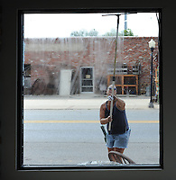NWA Democrat-Gazette/ANDY SHUPE<br /> Penni Cannady washes windows Tuesday, Sept. 29, 2015, at The Locals Craft and Flea Market in downtown Prairie Grove. Cannady and her best friend April Mosher work for Mr. T's Window Cleaning in Siloam Springs and wash windows throughout the downtown area.