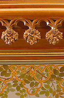 The intricately carved cornice with leaves and fruits echoes the motifs on the hand-painted wall beneath