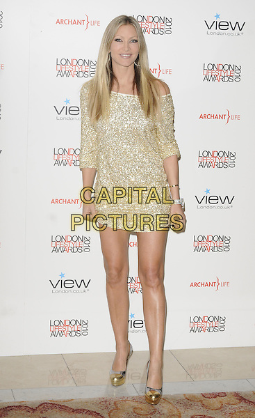 CAPRICE BOURRET.The London Lifestyle Awards, Park Plaza Riverbank Hotel, London, England..October 7th, 2010.full length gold dress off the shoulder platform shoes metallic sequins sequined .CAP/CAN.©Can Nguyen/Capital Pictures.