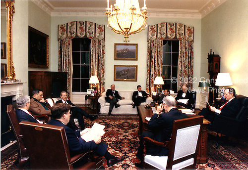 United States President George H.W. Bush, far right, meets with National Security Advisor General Brent Scowcroft, right foreground, White House Chief of Staff Governor John Sununu, left foreground, Central Intelligence Agency (CIA) Director Robert Gates, Chairman of the Joint Chiefs of Staff, General Colin Powell, Secretary of State James A.  Baker, White House Press Secretary Marlin Fitzwater, Vice President Dan Quayle, Richard Haas and Secretary of Defense Dick Cheney in the residence office to discuss the United States response to the Soviet peace plan with Iraq in Washington, DC on February 21, 1991.