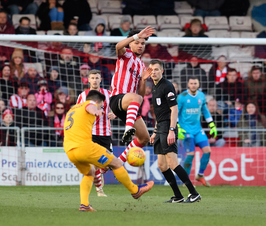 Northampton Town's David Buchanan under pressure from Lincoln City's Lee Angol<br /> <br /> Photographer Chris Vaughan/CameraSport<br /> <br /> The EFL Sky Bet League Two - Lincoln City v Northampton Town - Saturday 9th February 2019 - Sincil Bank - Lincoln<br /> <br /> World Copyright © 2019 CameraSport. All rights reserved. 43 Linden Ave. Countesthorpe. Leicester. England. LE8 5PG - Tel: +44 (0) 116 277 4147 - admin@camerasport.com - www.camerasport.com