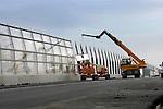 HARDINXVELD-GIESSENDAM - In Hardinxveld-Giessendam worden door Duitse bouwvakkers in opdracht van Rijkswaterstaat, glazen panelen gemonteerd die onderdeel zijn van een lange geluidswand. ruimt een sloopbedrijf de laatste resten op van de toerit van een oud boogviaduct over snelweg A15. De werkzaamheden zijn onderdeel van de verbreding van de snelweg A15 die voorlopig nog het meeste, en zwaarste vrachtwagenverkeer van Nederland te verduren krijgt. Naast een verbreding van de snelweg worden gelijktijdig viaducten vernieuwd en op- en afritten gewijzigd. ANP PHOTO COPYRIGHT TON BORSBOOM