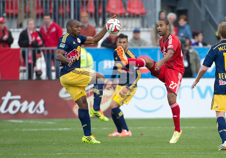 Toronto, Ontario - May 17, 2014: Toronto FC forward Luke Moore #27 battles for a ball with New York Red Bulls defender Jamison Olave #4 in the second half during a game between the New York Red Bulls and Toronto FC at BMO Field. Toronto FC won 2-0.