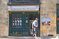 The restaurant Les Epicuriens in Saint Emilion, Bordeaux, a big man leaving the restaurant with a shirt that says boy