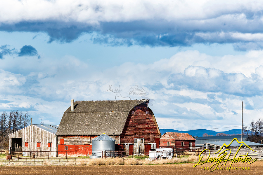A dynamic sky and a red barn decorate the landscape of Gooding Idaho.
