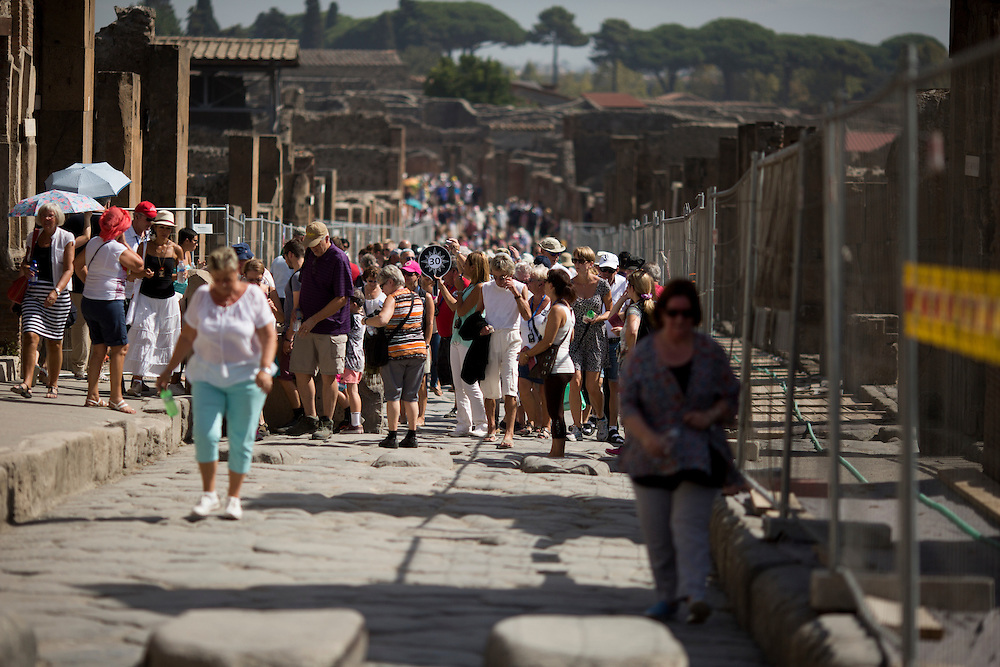 Tourists make their way down Via dell'Abbondanza, one of the main roads in the ruins, on Friday, Sept. 18, 2015, in Pompeii, Italy. The city of Pompeii was destroyed when nearby Mount Vesuvius erupted on August 24, AD 79. The town and its residents were buried and forgotten until the ruins were discovered and eventually excavated hundreds of years later. The ruins are one of Italy's top tourist attractions today. (Photo by James Brosher)