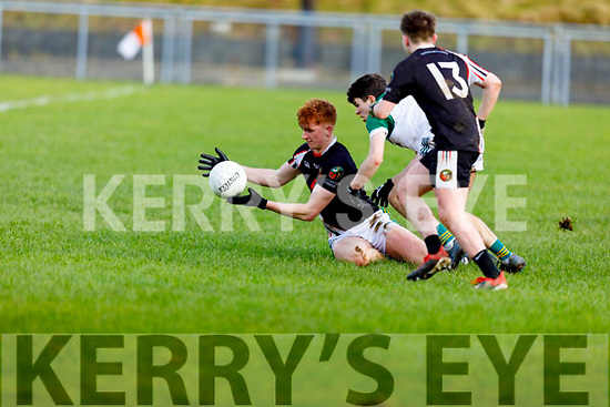Gaelcholaiste Chiarrai's Caolán Ó Conaill attempts to hand pass as he is under pressure from Ted Moloney of Coláiste Íde agus Iosef, Abbeyfeale in the Munster Colleges C Football Final in Brosna on Friday