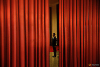 A security agent guards the area behind curtains inside the Great Hall of the People where sessions of the National People's Congress (NPC) are taking place in Beijing March 6, 2016.   REUTERS/Damir Sagolj