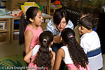 New York City preschool ages 3-5 music dance activity female teacher working with group of children horizonal